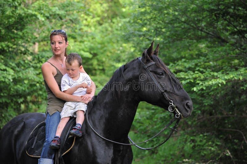 Mutter, Sohn und schwarzes Pferd stockbild