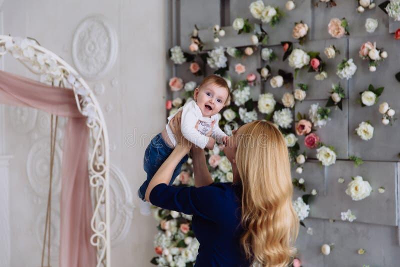 Mutter spielt mit ihrer Tochter, die ihre Arme ausgestreckt hält, und das Babylachen glücklich, mag sie lizenzfreies stockfoto
