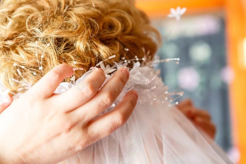 Mutter trägt den Heiratsschleier der Tochter stockbild