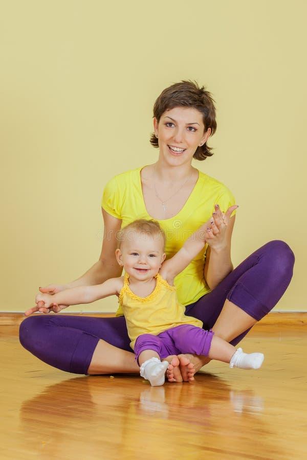 Mutter tut körperliche Bewegungen mit ihrer Tochter stockbilder