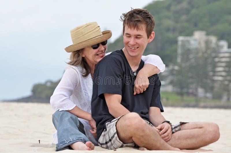 Mutter- u. Erwachsensohn, der ein Lachen auf Strand teilt stockbilder