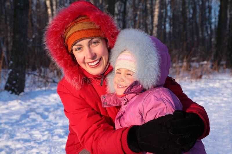 Mutter umfaßt Tochter im Winter lizenzfreie stockbilder