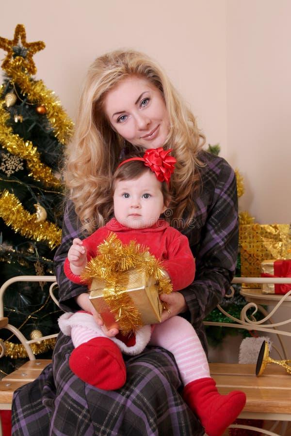 Mutter und Baby als Sankt-Helfer am Weihnachten lizenzfreies stockbild