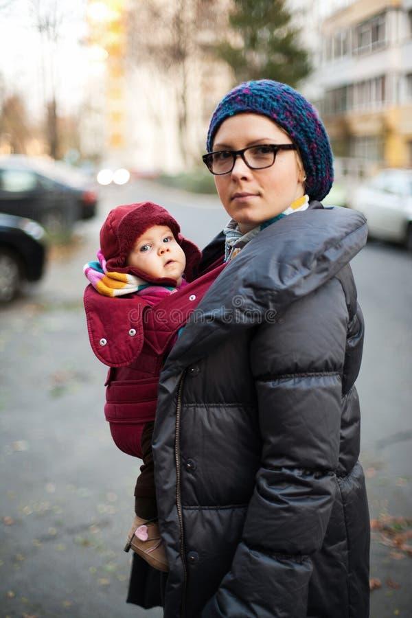 Mutter und Baby in den Mänteln stockfotos