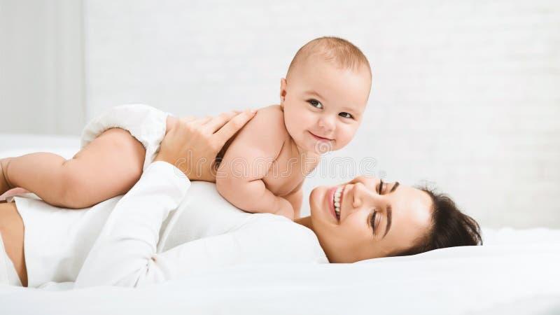 Mutter und Baby in der Windel, die im Schlafzimmer spielt lizenzfreie stockfotos