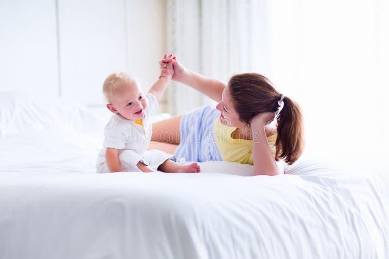 Mutter und Baby, die im Schlafzimmer spielen stockfotografie