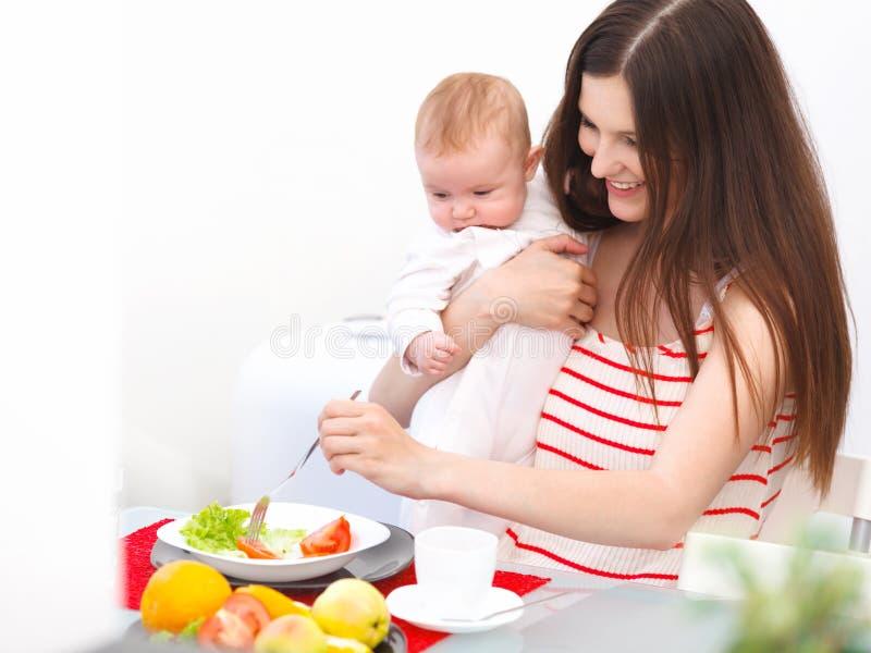 Mutter und Baby, die zu Hause essen Glückliches lächelndes Familien-Portrait lizenzfreie stockbilder