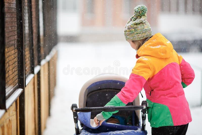 Mutter und Baby im Spaziergänger auf Weg, Wetter des verschneiten Winters Schneefälle, Blizzard, im Freien lizenzfreie stockbilder