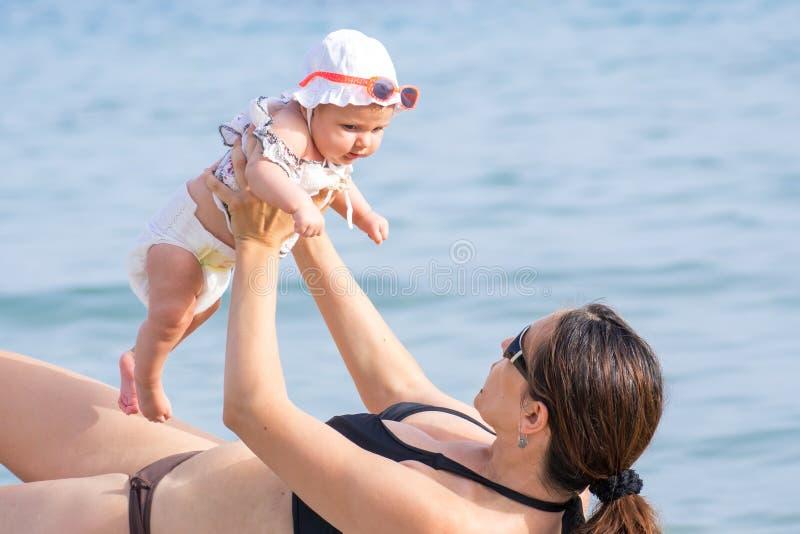Mutter und Baby in Meer stockbilder