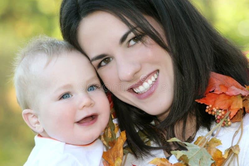 Mutter und Baby mit Blättern - Fall-Thema lizenzfreie stockfotos