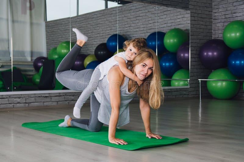 Mutter und Baby tun Übungen zusammen in der Turnhalle lizenzfreies stockfoto