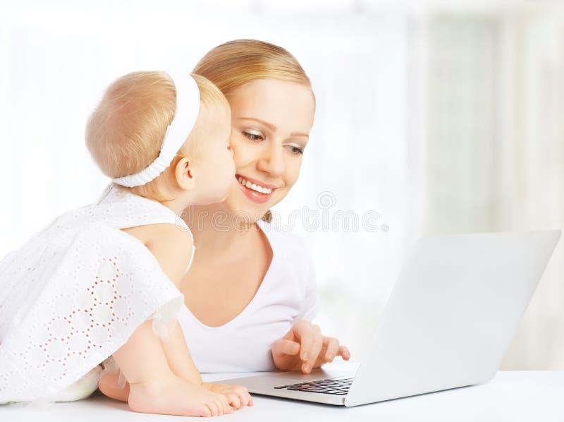 Mutter und Baby zu Hause unter Verwendung der Laptop-Computers stockbild