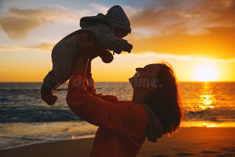 Mutter- und Babyschattenbilder bei Sonnenuntergang auf dem Meer setzen auf den Strand stockfotos