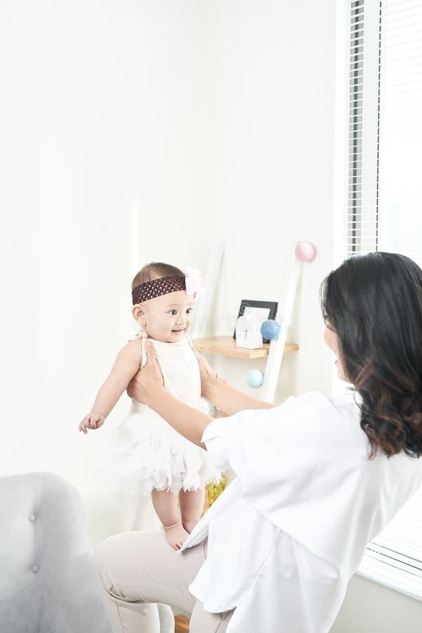 Mutter- und Babytochter gl?cklich und sch?nes Haus, das zusammen auf dem Boden auf Fensterhintergrund spielt stockfotos
