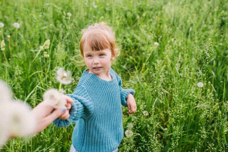 Mutter und das wenig Tochterspiel auf einer grünen Wiese mit Löwenzahn lizenzfreie stockfotografie