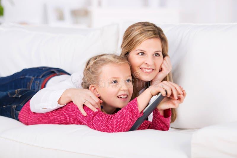 Mutter und daugher, die auf dem Sofa fernsieht liegt lizenzfreies stockbild