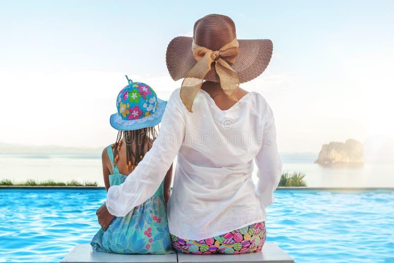 Mutter und daugher, die am Unendlichkeitspool sitzen lizenzfreies stockfoto