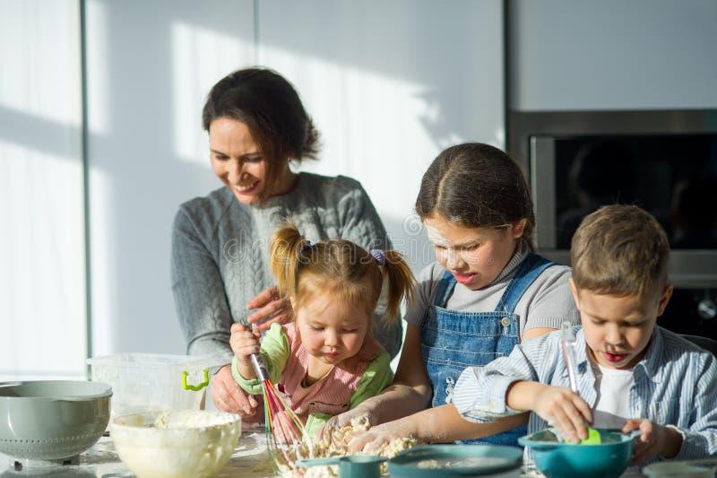 Mutter und drei Kinder bereiten etwas vom Teig vor lizenzfreie stockbilder