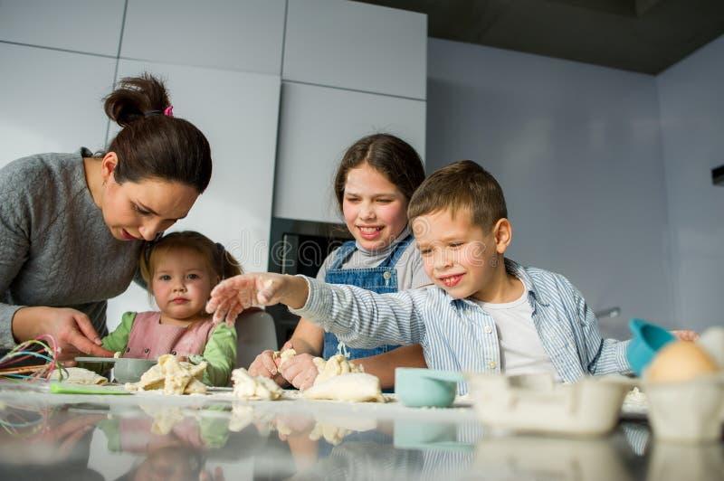Mutter und drei Kinder bereiten etwas vom Teig vor stockbild
