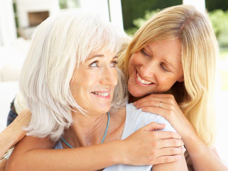 Mutter-und Erwachsen-Tochter, die auf Sofa sich entspannt lizenzfreies stockfoto