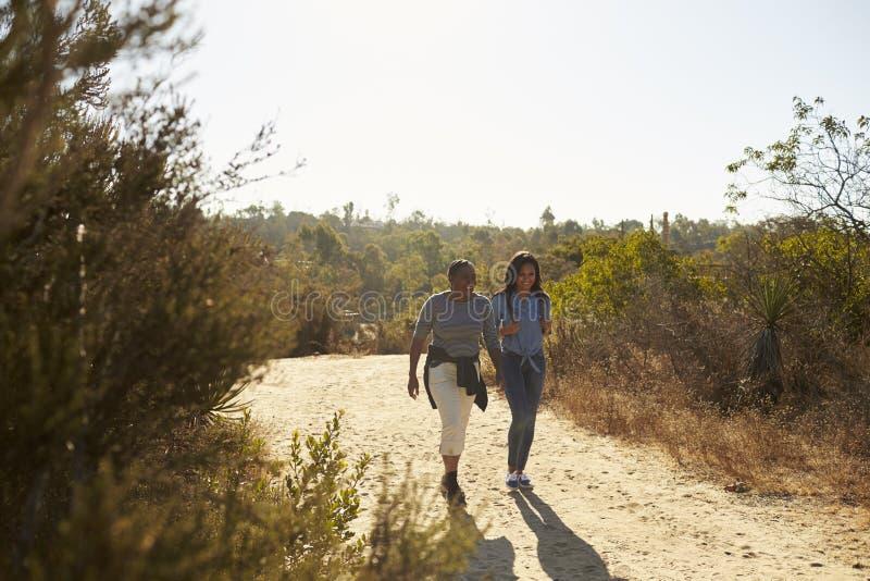 Mutter-und Erwachsen-Tochter, die draußen in der Landschaft wandert stockfotos