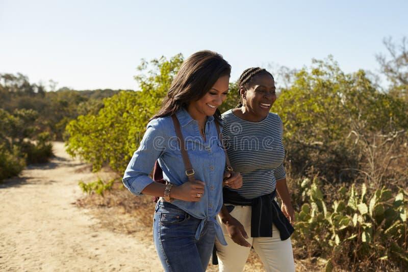 Mutter-und Erwachsen-Tochter, die draußen in der Landschaft wandert lizenzfreie stockfotos