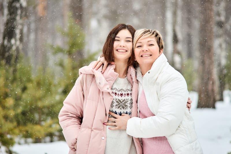 Mutter und erwachsene Tochter, die in Winterwaldschneefälle gehen lizenzfreies stockbild