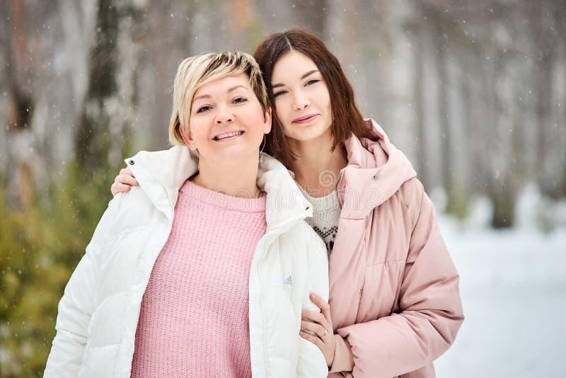 Mutter und erwachsene Tochter, die in Winterwaldschneefälle gehen stockbilder