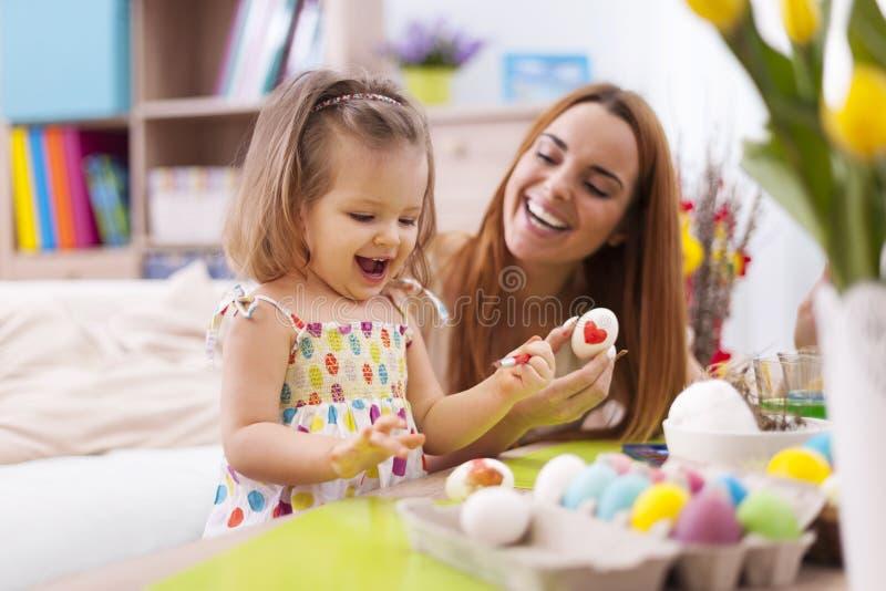 Mutter und ihr Baby, die Ostereier malen lizenzfreie stockfotografie