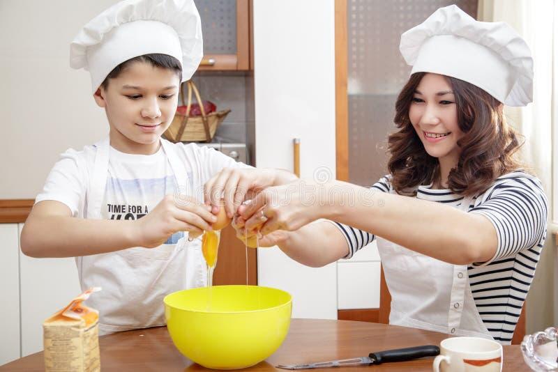 Mutter und ihr Kind in den weißen Chefhüten, die ein Omelett in der Küche zubereiten stockfotografie