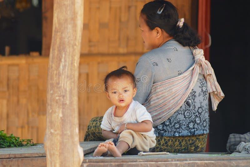 Mutter und ihr Kind sitzen außerhalb ihres Hauses am traditionellen Dorf nahe Luang Prabang, Laos lizenzfreies stockfoto