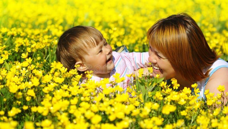 Mutter und ihr Kinderspiel auf Wiese lizenzfreie stockbilder
