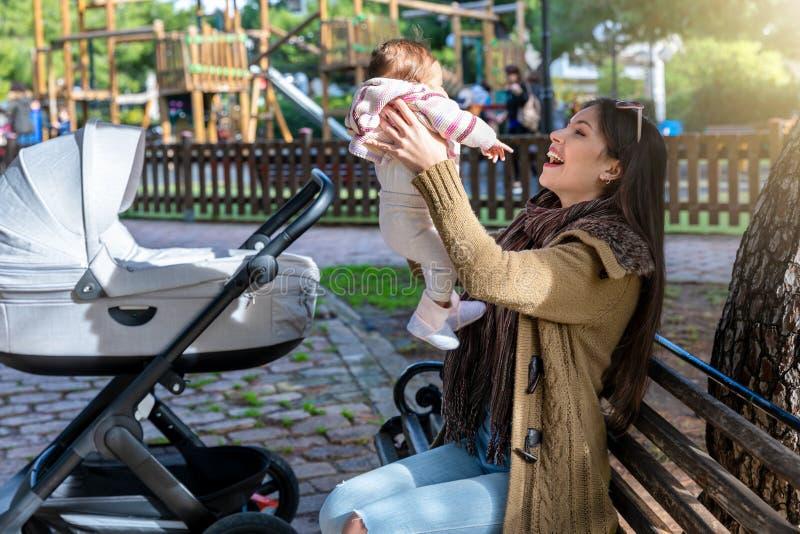 Mutter und ihr neugeborenes Baby auf einer Parkbank lizenzfreie stockfotografie