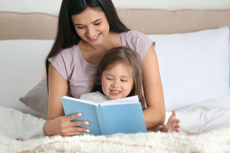 Mutter und ihr Tochterlesebuch zusammen zu Hause stockbilder