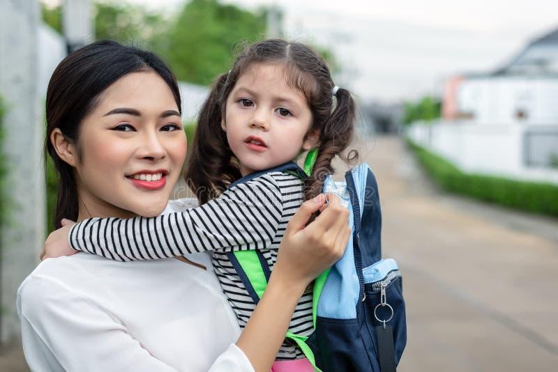 Mutter und ihr Tochterporträt zusammen bevor dem Gehen zu schulen Zur?ck zu Schule und Bildungskonzept Süßes Haupthaus und glückl stockfotos