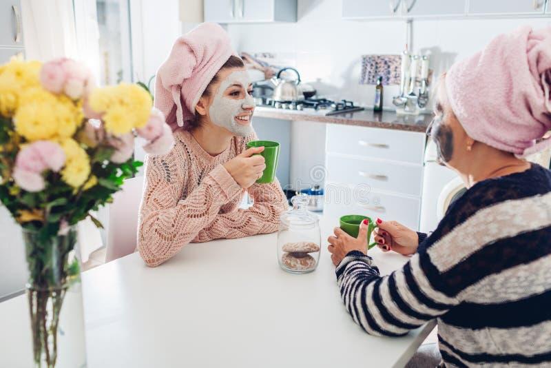 Mutter und ihr trinkender Tee der erwachsenen Tochter mit Gesichtsmasken trafen zu Frauen, die auf Küche kühlen und sprechen stockfotografie
