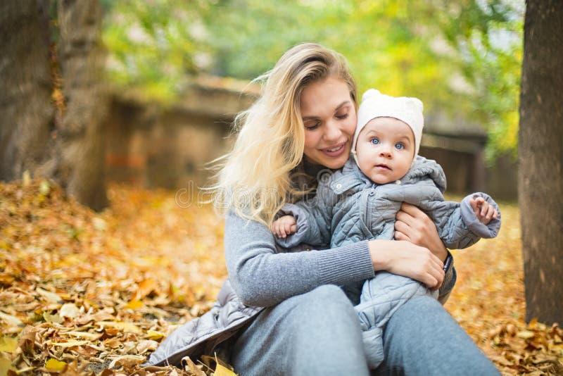 Mutter und ihr wenig Tochterspiel, die draußen auf Herbstweg in der Natur streicheln stockfoto