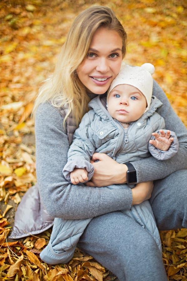 Mutter und ihr wenig Tochterspiel, die drau?en auf Herbstweg in der Natur streicheln lizenzfreies stockfoto