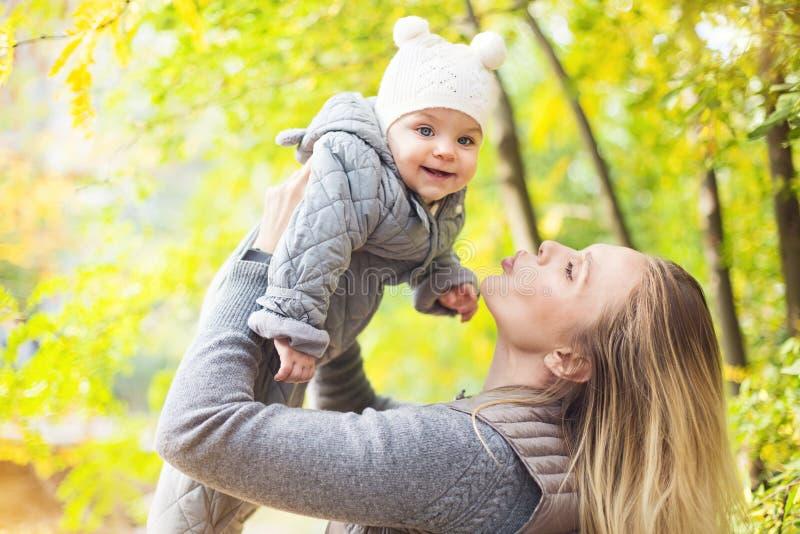 Mutter und ihr wenig Tochterspiel, die drau?en auf Herbstweg in der Natur streicheln stockfotografie