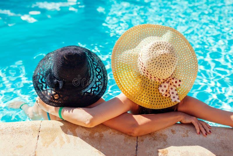Mutter und ihre erwachsene Tochter, die im HotelSwimmingpool sich entspannen Leute, die Ferien genießen Mutter`s Tag lizenzfreies stockbild