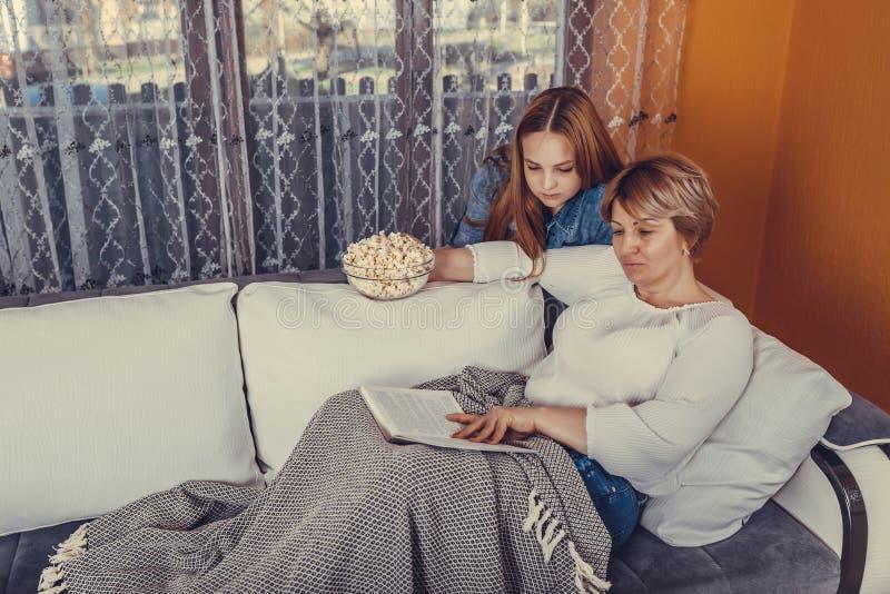 Mutter und ihre jugendliche Tochter sind Lesebuch und Essenpopcorn stockfotos