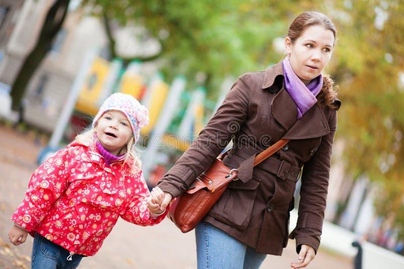 Mutter und ihre Tochter, die Hand in Hand gehen lizenzfreies stockbild
