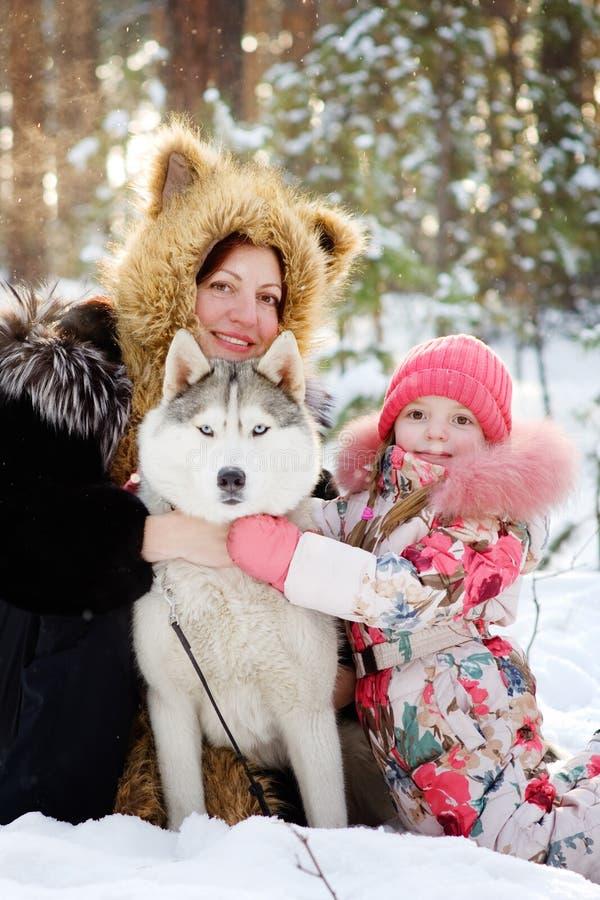 Mutter und ihre Tochter, die Schlittenhunde umarmen stockfotografie