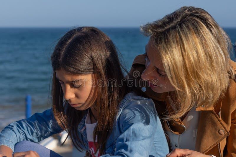 Mutter und jugendliche Tochter, die durch das Mittelmeer sprechen lizenzfreie stockfotos