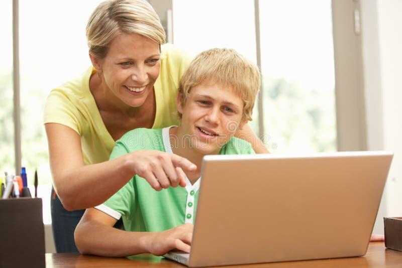 Mutter und jugendlicher Sohn, der zu Hause Laptop verwendet lizenzfreie stockfotos