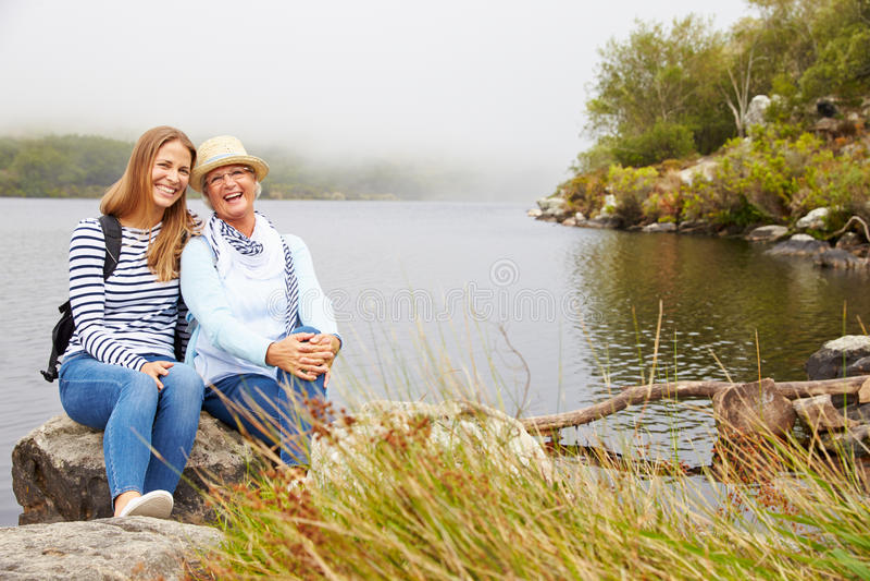 Mutter und junge erwachsene Tochter, die durch einen See, Kamera betrachtend sich entspannt lizenzfreie stockfotos