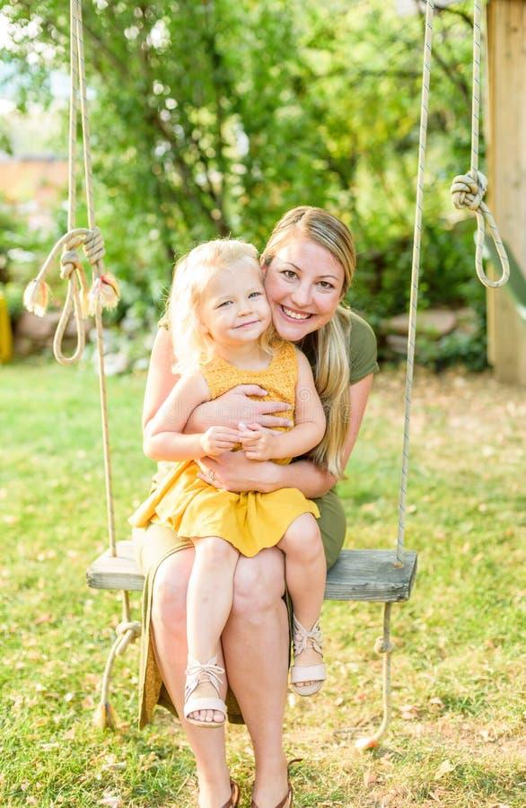 Mutter und junge Tochter auf Hinterhofschwingen stockfotos