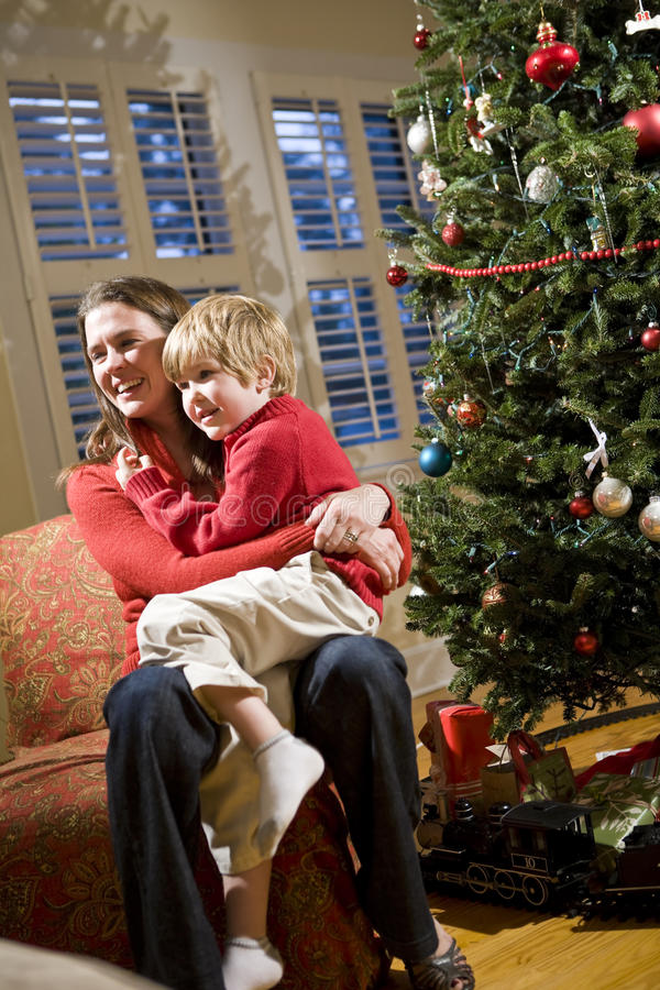 Mutter und junger Sohn, die durch Weihnachtsbaum sitzen stockbilder