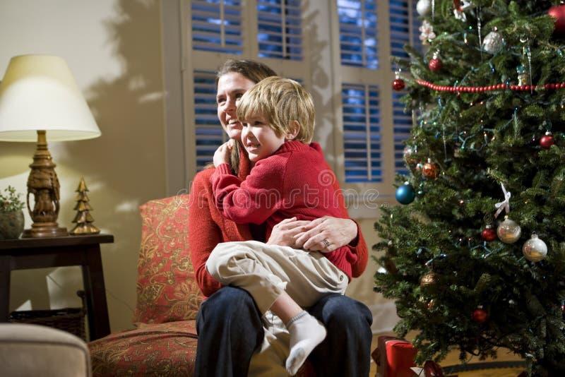 Mutter und junger Sohn, die durch Weihnachtsbaum sitzen lizenzfreie stockfotos