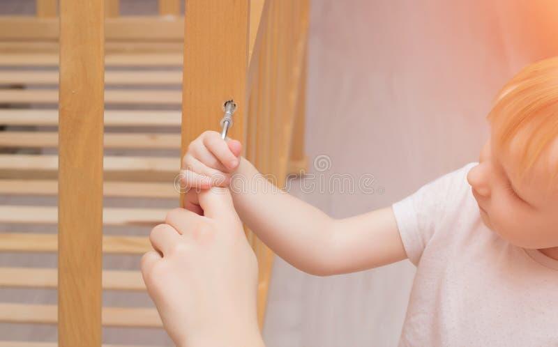 Mutter und Kind bauen eine Krippe, Nahaufnahme, Kaukasier, hölzerne Krippe der Installation zusammen lizenzfreie stockfotos